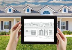 Female Hands Holding Computer Tablet with House Drawing on Screen. Photo Behind stock images