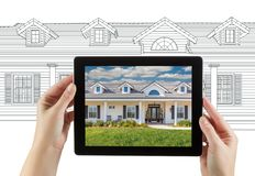 Female Hands Holding Computer Tablet with House Photo on Screen. & Drawing Behind royalty free stock photo