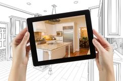 Female Hands Holding Computer Tablet with Kitchen on Screen. & Drawing Behind stock photography