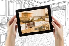 Female Hands Holding Computer Tablet with Kitchen on Screen. & Drawing Behind royalty free stock photos