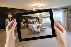 Female Hands Holding Computer Tablet In Room with Photo on Screen.  stock image
