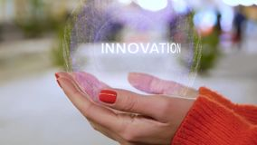 Female hands holding a conceptual hologram with text Innovation. Woman with red nails and sweater with future holographic technology on a blurred background of stock video footage