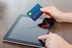 Female hands holding credit card and a computer on the table in Stock Images