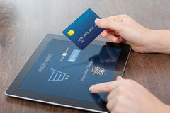 Female hands holding credit card and a tablet in the office and stock photo