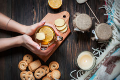 Female hands holding cup black tea with lemon, ginger and cookies on dark wood Stock Photography