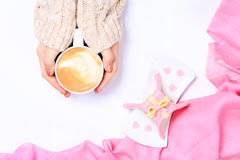 Female hands holding cup of cappuccino. Gift alike dessert with Royalty Free Stock Photos