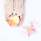 Female hands holding cup of cappuccino. Gift alike dessert with Royalty Free Stock Photography
