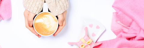 Female hands holding cup of cappuccino. Gift alike dessert with Royalty Free Stock Images