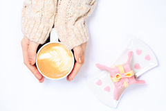 Female hands holding cup of cappuccino. Gift alike dessert with Stock Photography