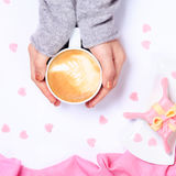 Female hands holding cup of cappuccino. Gift alike dessert with Stock Photos