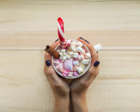 Female hands holding cup of chocolate with marshmallow on rustic Royalty Free Stock Photos