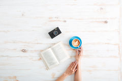 Female hands holding cup of coffee over wooden table Stock Image