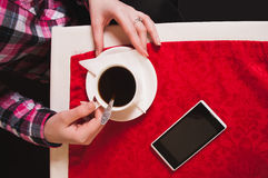 Female hands holding Cup of coffee on the table with a red tablecloth, Royalty Free Stock Photography