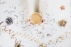 Female hands holding cup of coffee. On white rustic sparkling background. Festive backdrop for holidays. Flat lay Royalty Free Stock Image