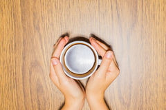 Female hands holding cup of coffee on wooden background Stock Photos