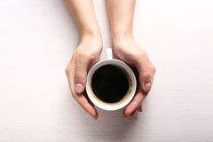 Female hands holding cup of coffee on wooden background Royalty Free Stock Image