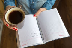 Female hands holding a cup of hot coffee and notebook Royalty Free Stock Images