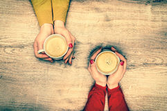 Female hands holding a cup of hot coffee - retro style Stock Photography