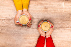 Female hands holding a cup of hot coffee. On wooden table Stock Images