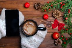 Female hands holding a cup with a hot drink and a smartphone over a wooden table top view. Hands in mittens are holding a mug of hot chocolate over the stock image