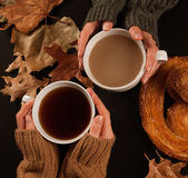 Female hands holding cups of coffee. Cozy autumn mood Royalty Free Stock Photo