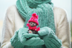 Female hands holding cute teddy bear. Woman hands in teal mittens showing teddy bear gift dresses in pink knitted hat and scarf. Stock Photos