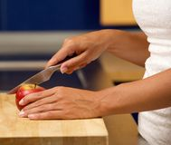 Female hands holding cutting apple in kitchen Royalty Free Stock Photos