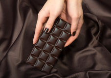 Female hands holding the dark chocolate bar Royalty Free Stock Photography