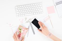 Female hands holding decorative envelope and smartphone with blank screen at workplace. Top view of female hands holding decorative envelope and smartphone with Royalty Free Stock Photography
