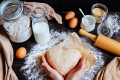 Female hands holding dough in heart shape top view. Baking ingredients on the dark wooden table Royalty Free Stock Photos