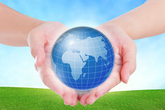 Female hands holding on earth global on grassland. Royalty Free Stock Photos