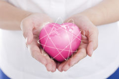 Female hands holding on earth global heart. Royalty Free Stock Photo