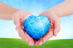 Female hands holding on earth global heart on grassland. Royalty Free Stock Photography