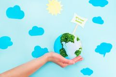 Female Hands holding Earth paper and green sprouts collage model with It`s our home pointer on blue background with paper sun and. Clouds. Earth in your hands Royalty Free Stock Photo