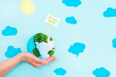 Female Hands holding Earth paper and green sprouts collage model with It`s our home pointer on blue background with paper sun and. Clouds. Earth in your hands Stock Photo