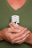 Female Hands Holding Energy Saving Light Bulb. Against Green Shirt Stock Image