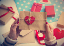 Female hands holding envelope with a heart. To give it to someone Stock Image