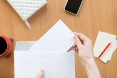 Female hands holding an envelope with a sheet over the office de Royalty Free Stock Image