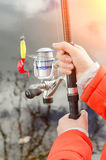 Female hands holding a fishing rod and lure. Stock Photography