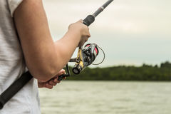 Female hands holding a fishing rod and twist the handle Stock Images