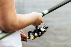 Female hands holding a fishing rod Royalty Free Stock Image