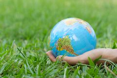 Female hands holding floating earth on natural green background. Earth day. stock photo