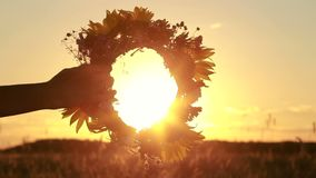 Female hands holding flower wreath in sunset light stock footage