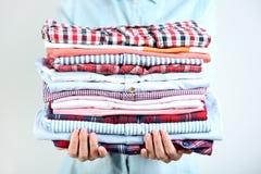 Folded shirts. Female hands holding folded shirts royalty free stock photos