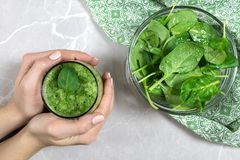 Female hands holding a fresh green spinach and kiwi smoothie royalty free stock image