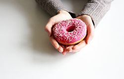 Female hands holding freshly baked sweet donuts with sprinkles. Top view .White background. Breakfast .Lifestyle concept stock images