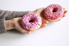 Female hands holding freshly baked sweet donuts with sprinkles. Top view .White background. Breakfast .Lifestyle concept stock image