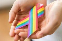 Female hands holding gay pride awareness ribbon royalty free stock image