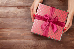 Female hands holding gift above wooden table Royalty Free Stock Image