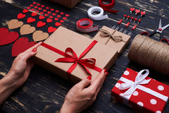 Female hands holding gift box before adding decorative elements Stock Photos